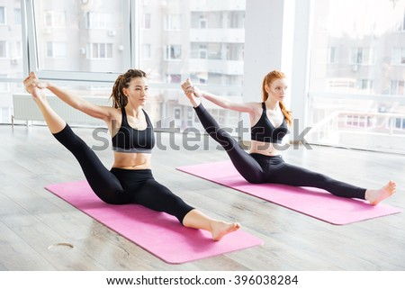 Two attractive young women stretching legs and practicing yoga in studio - stock photo