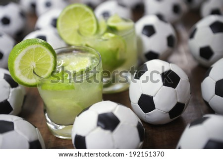Two authentic fresh lime caipirinhas with soccer footballs Brazilian culture - stock photo
