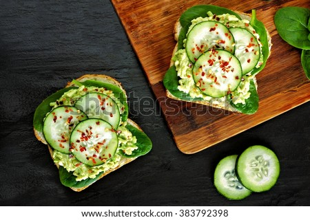 Two avocado toast sandwiches with cucumber and spinach on whole grain bread - stock photo