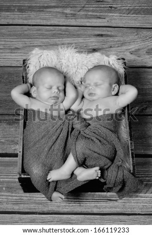 Two babies asleep with their hands tucked under their heads.