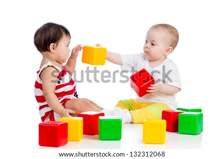 two babies or kids playing together with color toys - stock photo