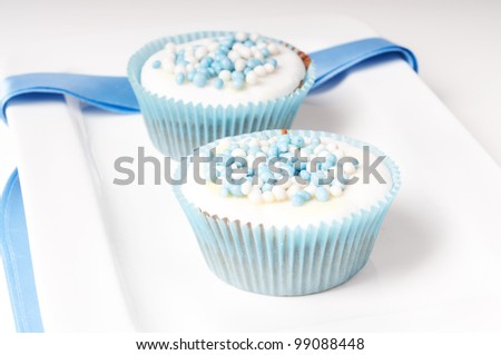 two baby blue cupcakes on a plate - stock photo