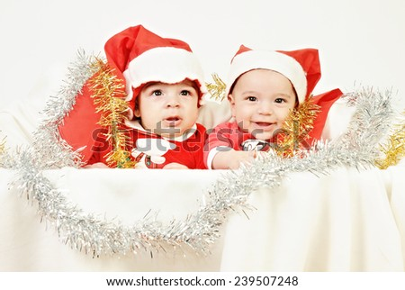 two baby boys wearing a santa claus red suit and a long red hat seating in a White basket with Christmas decorations isolated on White background - stock photo