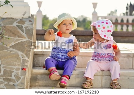 two baby friends sitting on the stairs