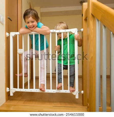 Two baby girls approaching safety gate of  stairs - stock photo