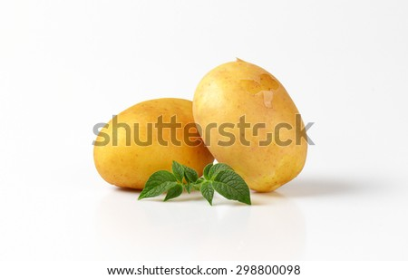 two baby potatoes with leaves on white background