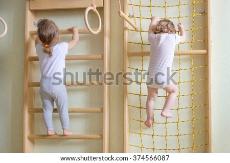 Two baby toddlers climbing up the gymnastic stairs.