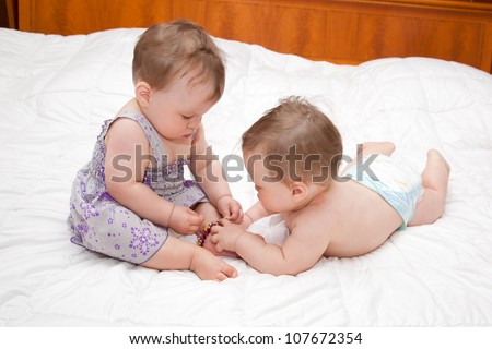 Two baby twins playing together