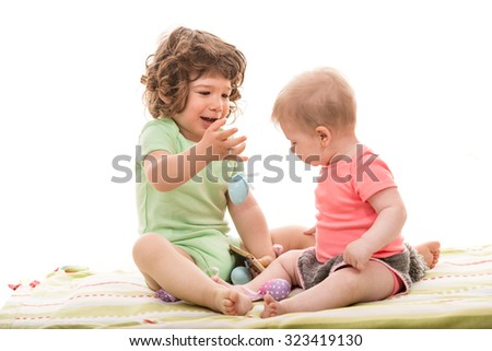Two babys playing with colorful Easter eggs against white background