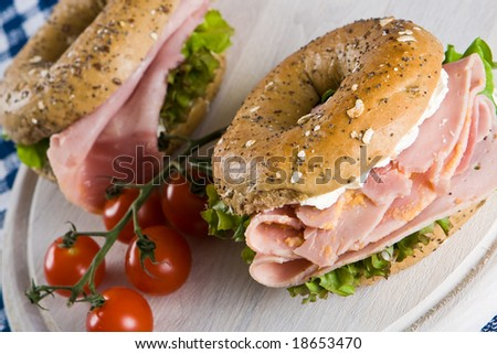 Two bagels with honey roasted ham on a wooden board - stock photo