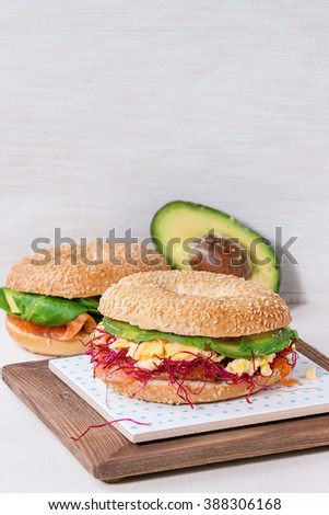 Two Bagels with salted salmon, spinach, beet sprouts, avocado and scrambled egg on ceramic tile over white stone table.