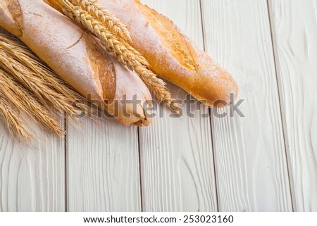 two baguettes and ears of wheat on old white wooden boards with copyspace  - stock photo