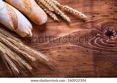 two baguettes ears of wheat and rye on vintage wooden board with organized copyspace food and drink concept  - stock photo