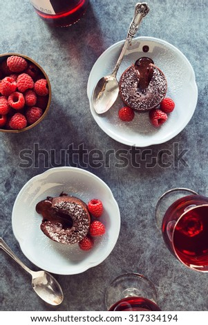 Two Baked Chocolate Lava Cakes with Raspberries and Red Wine - stock photo