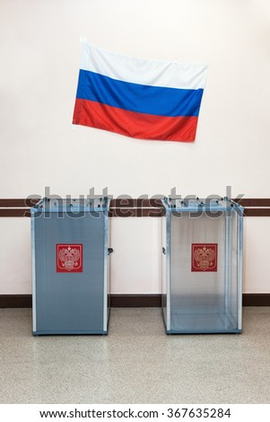 Two ballot boxes for voting in the elections with coat of arms Russia and the national flag of the Russian Federation hanging on the wall in the polling station.