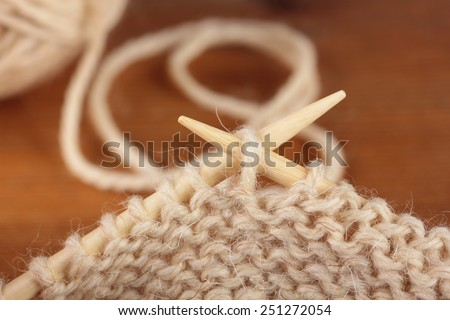 Two bamboo knitting needles in process of knitting - stock photo