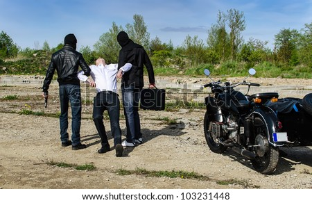 Two bandits kidnapped a businessman with a suitcase - stock photo