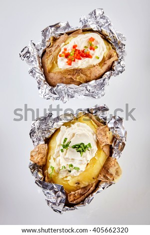 Two barbecued baked potatoes in tin foil topped with sour cream and garnished with chopped chives and peppers viewed from overhead still in the foil wrapping - stock photo