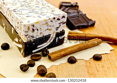 Two bars of beige and brown homemade soap, chocolate, cinnamon, coffee beans on old paper on the background of wooden boards - stock photo