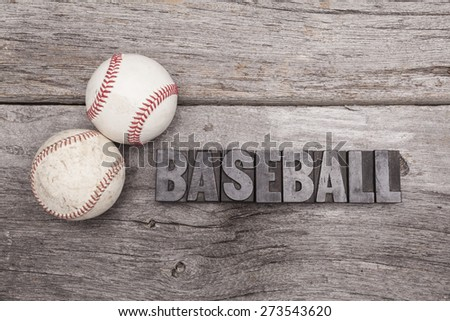 Two baseballs sit on a rustic wooden background. Sitting next to the balls is the word baseball spelled out in vintage printers type. - stock photo