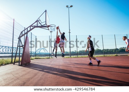 Two basketball players jumping for the ball - stock photo