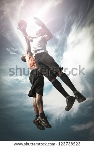 Two Basketball players playing street basket and jumping together to catch the ball