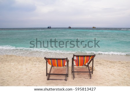 two beach beds , sea background