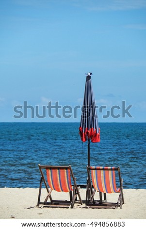 Two beach bench and beach umbrella on the white sand beach face to the sea or ocean