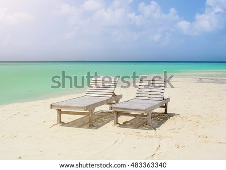 Two beach chairs on a sandy coast of the ocean