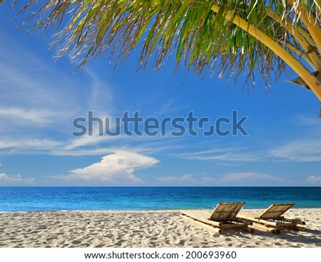 Two beach chairs on idyllic tropical palm beach -- Tropical vacations concept  - stock photo