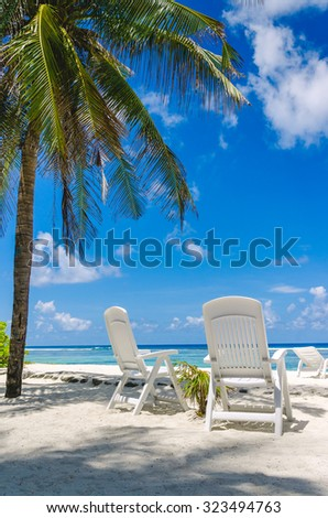Two beach chairs on perfect tropical white sand beach in Maldives