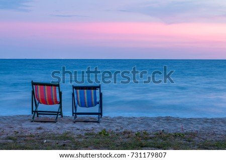 Two beach chairs on the beach at sunset with blue sea and colorful sky background. Travel and relax concept.