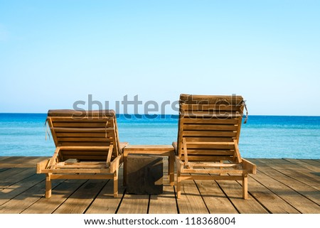 Two beach chairs on wooden floor with blue sea and clean sky on background