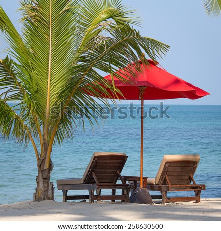 Two beach chairs, red umbrella and palm tree on the beach in Thailand - stock photo