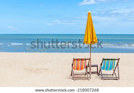 Two beach chairs with sun umbrella on beautiful beach. Concept for rest, relaxation and holiday. - stock photo