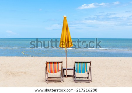 Two beach chairs with sun umbrella on beautiful beach. Concept for rest, relaxation, holiday. - stock photo