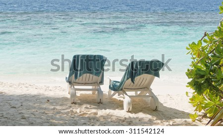 Two beach chairs with towels on them, holiday concept. - stock photo