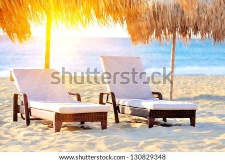 Two beach chairs with white umbrella - stock photo