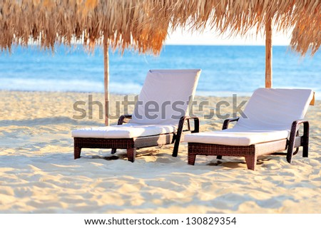 Two beach chairs with white umbrella - stock photo