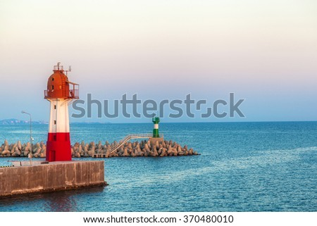 two beacons stand on pier by the sea - stock photo