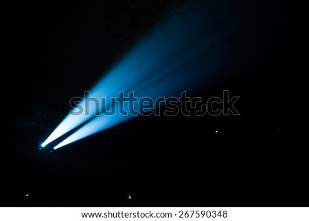 Two beams of searchlights in the dark concert hall. - stock photo
