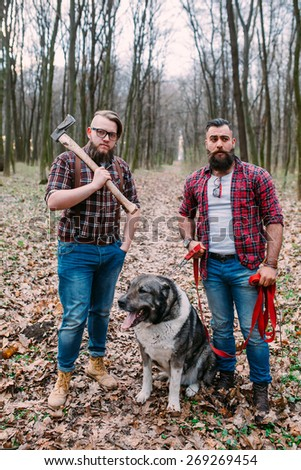 two bearded man with an ax and dog