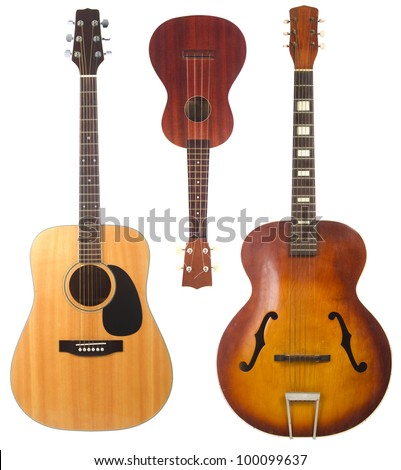 Two beautiful acoustic guitars, one antique one modern, and a ukulele isolated on white background