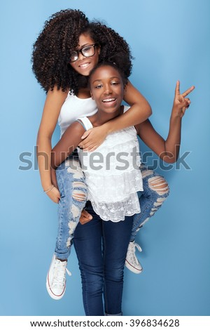 Two beautiful african american girls smiling, looking at camera. Sisters posing on blue background. Studio shot.Girls having fun. - stock photo