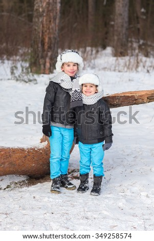 Two beautiful and cheerful brothers playing in the winter woods.
