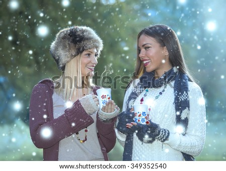 Two beautiful and happy smiling girls talking with a cup of hot coffee tea. Soft focus. Small depth of field. Low light. Winter concept