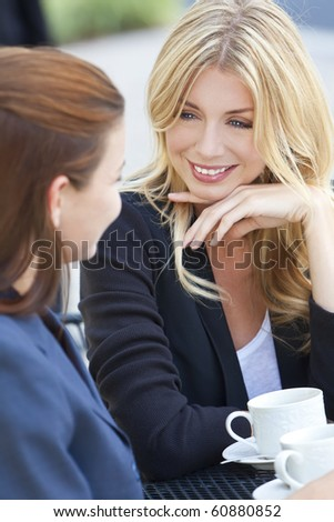 Two beautiful and sophisticated young women friends having coffee around a modern outdoor city cafe table