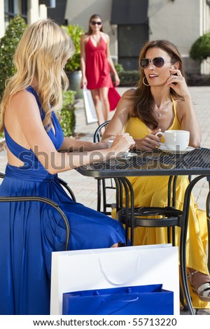 Two beautiful and sophisticated young women friends wearing sunglasses and having coffee around a modern city cafe table surrounded by shopping bags with their friend joining them in the background - stock photo