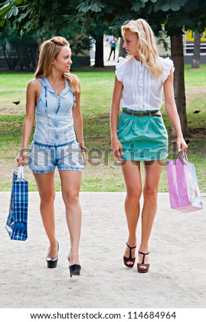 Two beautiful and young girl walking in the park after shopping in a store - stock photo