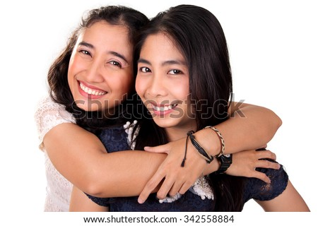 Two beautiful Asian female best friends embracing and smiling at camera, isolated on white background - stock photo